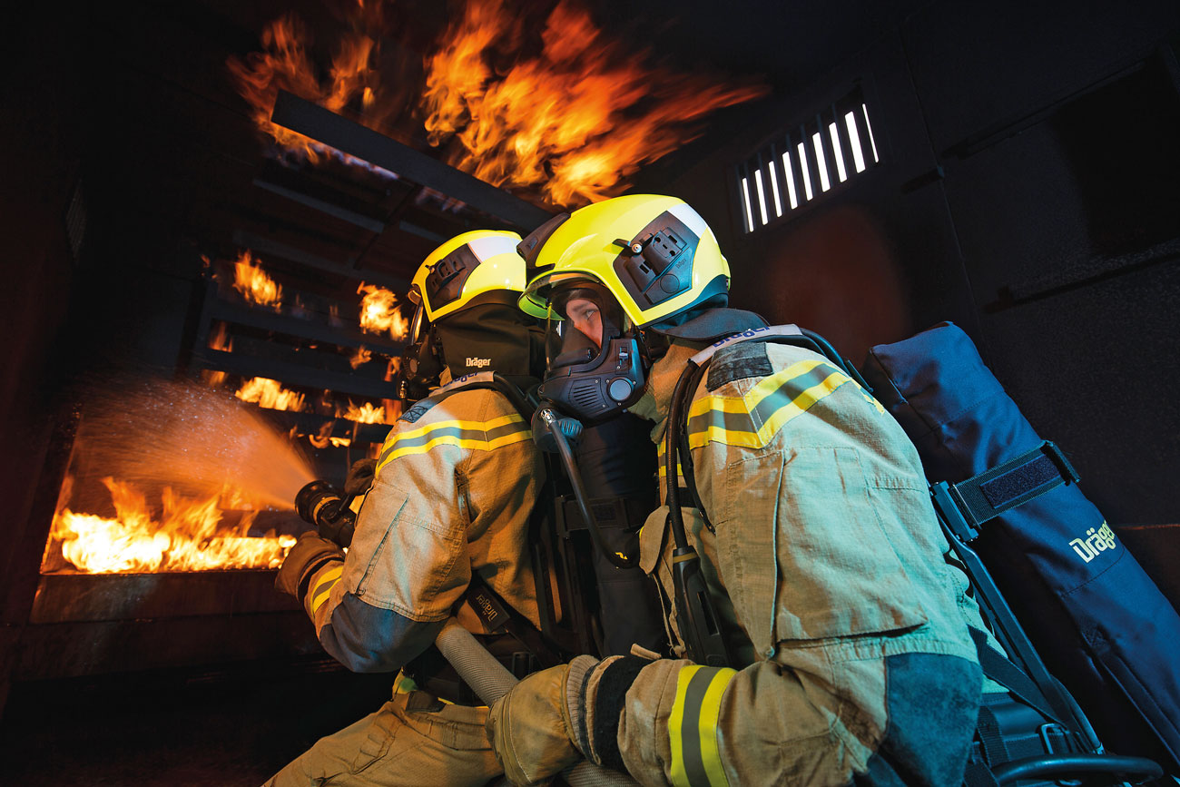 Firefighters wearing Dräger breathing apparatus within a training environment.