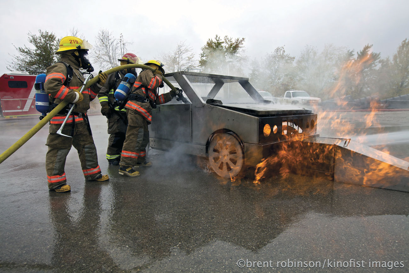 Firefighters extinguishing a fire in a realistic road accident training scenario with a Dräger Vehicle Fire training simulation.